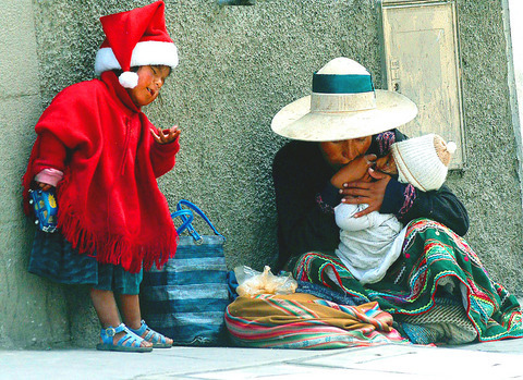 A beggar girl stands next to her mother on the streets of La Paz, Bolivia on Tuesday. Every year around the holidays an overwhelming number of beggars take ...
