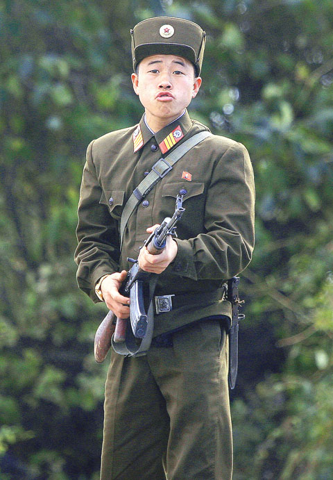An armed North Korean soldier raises his weapon. they execute person taking pictures with mobile phones