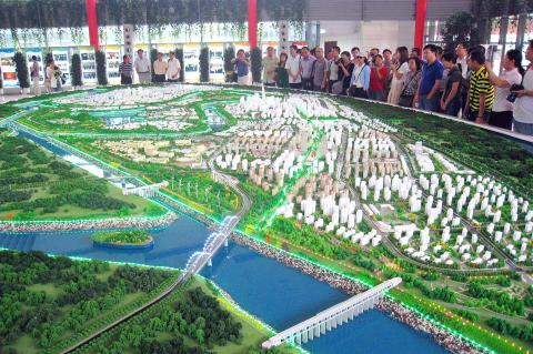 Visitors Look At A Model Of An Eco City Which Is Now Under Construction Near The Port Tianjin In North China On Sept 15
