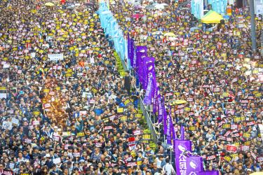 Tens of thousands march through HK, defying order