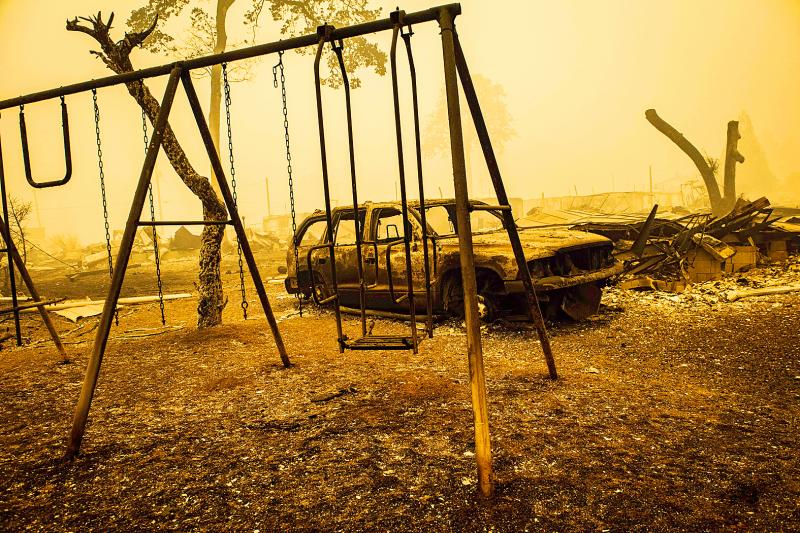A charred swing set and car remain after the passage of a wildfire in Gates Oregon on Thursday